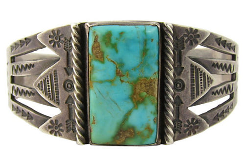 "Silver bracelet with turquoise set in plain bezel surrounded by stamped arrow and sunburst decoration. Made by a Native American bench smith in an urban factory setting, as was common during the 1920s. Interior, 7"" circumference with 0.9""L gap. Sold by Ruby + George on One Kings Lane Vintage and Market Finds"