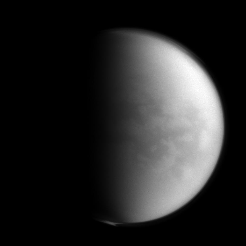 "Spying on Senkyo The Cassini spacecraft peers through Titan's thick clouds to spy on the region dubbed ""Senkyo"" by scientists. The dark features include vast fields of dunes, composed of solid hydrocarbon particles precipitated out of Titan's atmosphere. And Titan's southern pole is shrouded in the recently formed polar vortex. Titan, Saturn's largest moon, is 3,200 miles (5,150 kilometers) across. For more on Senkyo, see PIA08231. For a color image of the south polar vortex on Titan, see PIA14919. For a movie of the vortex, see PIA14920. Lit terrain seen here is on the Saturn-facing hemisphere of Titan. North on Titan is up and rotated 18 degrees to the right. The image was taken with the Cassini spacecraft narrow-angle camera on Jan. 5, 2013 using a spectral filter sensitive to wavelengths of near-infrared light centered at 938 nanometers. The view was obtained at a distance of approximately 750,000 miles (1.2 million kilometers) from Titan and at a Sun-Titan-spacecraft, or phase, angle of 79 degrees. Image scale is 4 miles (7 kilometers) per pixel. Image Credit:NASA/JPL-Caltech/Space Science InstituteImage Addition Date:2013-04-08"