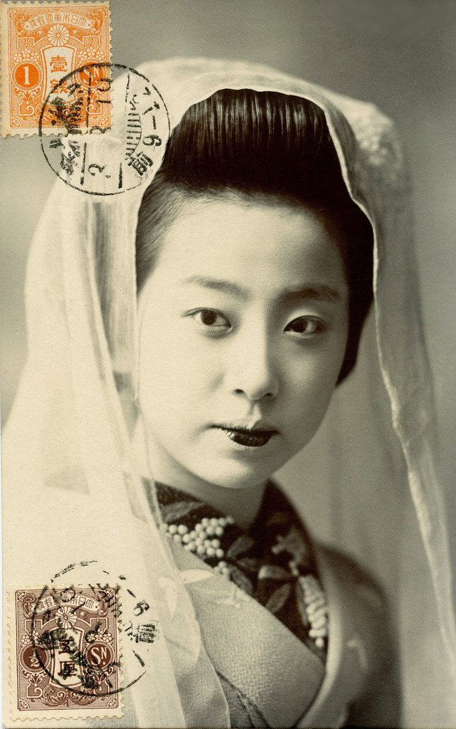 "Kyo-Maiko wearing a Tenugui 1914 (by Blue Ruin1) ""A fan or a tenugui (scarf) is often used in dancing, being manipulated to suggest all sorts of things as the occasion may require. To give a few examples in common practice: an open fan raised gradually in front signifies the rising sun; used in a drinking attitude it may represent a wine cup; a closed fan may be used to suggest a stick, a bow, an arrow, or a gun, etc.; a scarf may be doubled and thrust into the sash to indicate long and short swords worn by a samurai; when redoubled and held on the palm in a smoking attitude it may serve as a pipe; or it may be made to describe running water by holding one end of it and giving it a quick succession of jerks from one side to the other."""