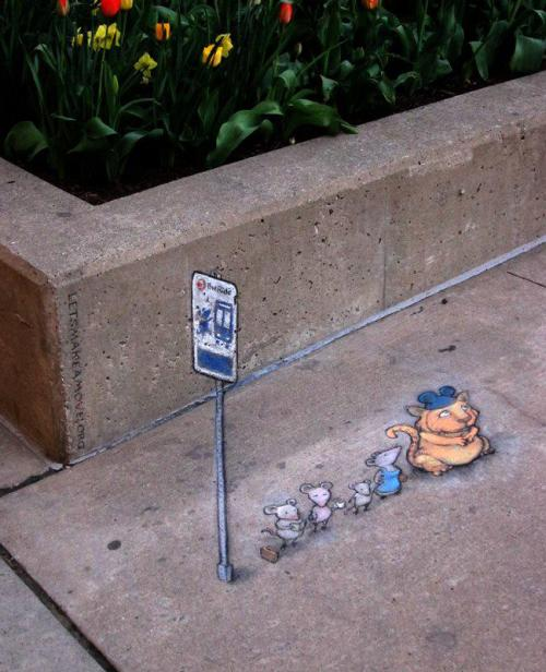 Street art by David Zinn in Ann Arbor, Michigan:   Apparently, there's a mouse line that stops at the northwest corner of William & Main; I'm guessing it's an express bus to the Creamery.  Note the URL in the background: Letsmakeamove.org is a month long competition that encourages employees throughout Ann Arbor to try alternative commuting during the month of May, organized by getdowntown.org and theride.org, the Ann Arbor Transportation Authority.