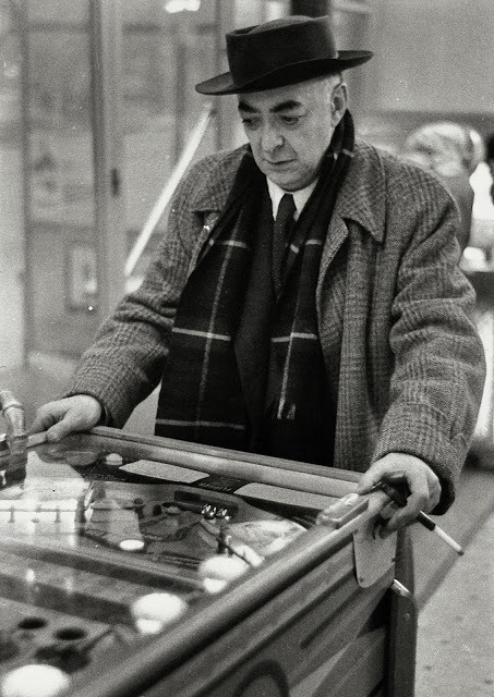 Hungarian photographer and visual artist Brassaï playing pinball.  Photo by his French colleague Willy Ronis, 1954.