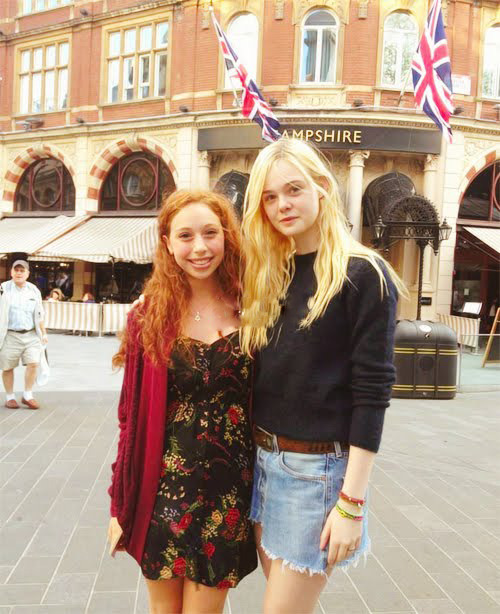 Elle Fanning emanates a golden glow while posing with a fan in London.