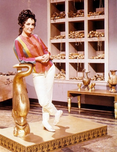 theswinginsixties:  Elizabeth Taylor posing with props from 'Cleopatra', 1963.