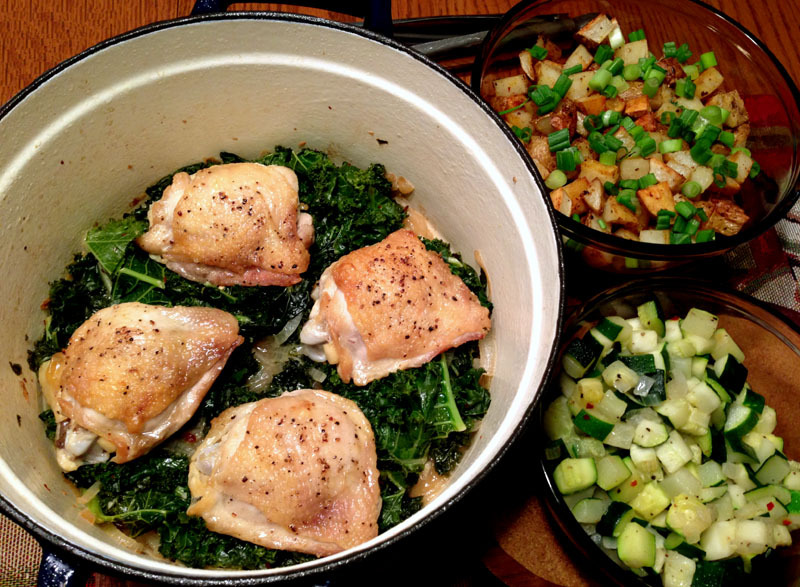 Seared Chicken Thighs, Braised Onions and Kale, Sauteed Zucchini, and Roasted Potatoes topped with Green Onions All of this for under $10. I feel like Melissa d'Arabian in this bitch.