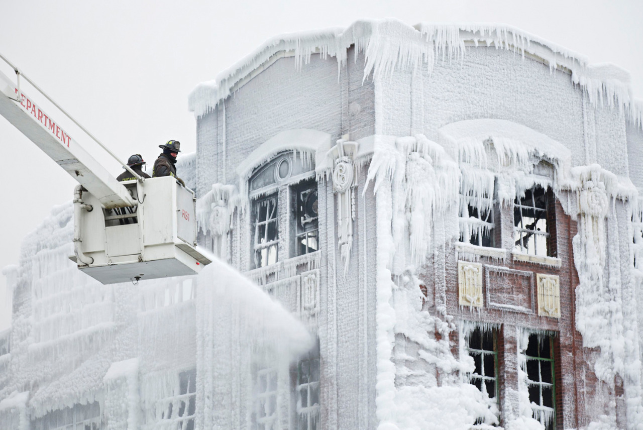 Firefighters spray down hot spots on an ice covered warehouse that caught fire in Chicago, USA, on January 23, 2013. The temperatures were well below freezing and the spray from the fire hoses encased everything below in ice, including buildings, vehicles, and some firefighting gear. Photo by Reuters/John Gress.