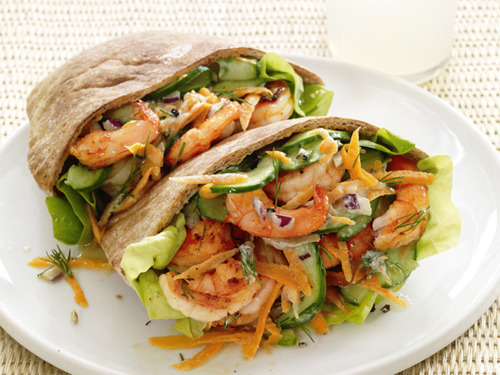 prettygirlfood:  Shrimp Salad Pitas Makes 4 Sandwiches Ingredients 1/2 small red onion, finely chopped 1 1/2 pounds medium shrimp, peeled, deveined and halved crosswise 2 tablespoons extra-virgin olive oil 1/2 teaspoon hot paprika Kosher salt and freshly ground pepper 1/2 cup 2% Greek yogurt 1 medium carrot, coarsely grated 1 Kirby cucumber, halved lengthwise, seeded and thinly sliced 1 tablespoon chopped fresh dill 1 lemon 4 whole-wheat pitas 8 Bibb lettuce leaves Directions  Preheat the broiler. Soak the chopped onion in a bowl of cold water while you prepare the shrimp. Toss the shrimp with the olive oil, paprika, 1/4 teaspoon salt, and pepper to taste on a rimmed baking sheet. Spread in an even layer and broil until the shrimp are opaque, about 4 minutes. Transfer to a bowl and let cool. Wash and dry the baking sheet. Drain the onion and add to the shrimp along with the yogurt, carrot, cucumber, dill, and salt and pepper to taste. Grate in 1 teaspoon lemon zest and squeeze in about half of the lemon juice. Lay the pitas on the baking sheet and toast under the broiler. Cut the pitas in half and fill with the lettuce and shrimp salad.