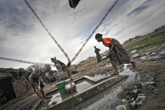 Photo: Displaced people bathe at a water pump in a camp outside Sittwe in Rakhine state. Myanmar 2013 © Kaung Htet Myanmar: Violence and Intimidation Leave Tens of Thousands Without Medical Care Eight...