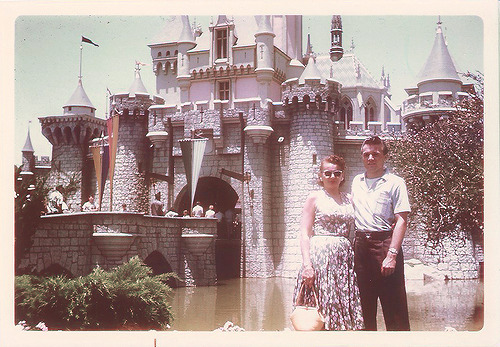 disneyhips:  Couple in front of Sleeping Beauty Castle, 1950s.
