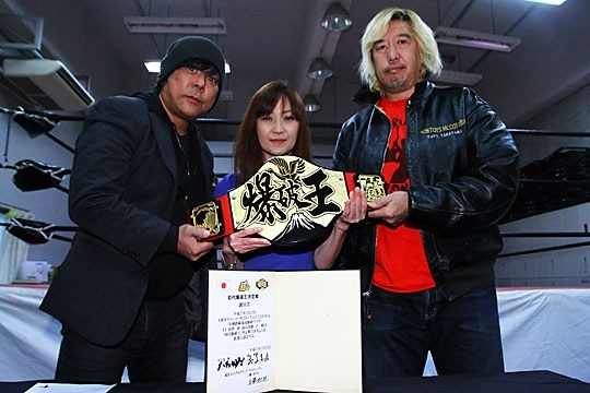 "[Super Fireworks News] The official ""Blast King"" belt has been unveiled as Atsushi Onita and Yoshihiro Takayama took part in the official title signing heading into tomorrow's first ever Cho Hanabi show.The Adviser of the Cho Hanabi shows Megumi Kudo attended the press as well to announce the official match type to be a ""No-rope Barbed-wire Electric Current Blast Double Bat Double Hell Death Match"". Takayama stated that he is looking to revenge against Onita as this will be the third time they have faced in the last year, as he has gotten stronger with each and every time he has competed in death matches. Takayama then stated that the new belt is definitely for him as he looks to be crowned the very first champion. Onita though as the pioneer of blast death matches boasts his own confidence heading into the match as he aims to continue showing ""Jado aka the evil course"" as is ever lasting.As originally mentioned the main plate of the ""Blast King / 爆破王"" belt has been made of granite and dusted with a old overlay. The crane on the top of the belt represents a symbol in Japan (long life and happiness), the mountain, Mt. Fuji, of course being another symbol of Japan, then the two plates on the side representing ""the world"" and style of ""hardcore"". Onita stated that this is he very pleased with how the belt came out and hopes that it can become another treasure of Japanese pro-wrestling.Below is the announced event card…Noodle Norio Presents Naniwa Cho Hanabi (Super Fireworks) ~ First Blast King Championship Finals ~, 1/23/2015 [Fri] 18:30 @ BODYMAKER COLOSSEUM, 2nd Stadium in Osaka(1) Jado-gun vs Osaka-gun 6 Man Tag Match: Ichiro Yaguchi, Hideki Hosaka & Kenichi Fuji vs. GUNSO, YO-HEY & HAYATA(2) Congratulations! Miss Mongolia Wedding Anniversary ~ FMW OG Set Match: Miss Mongolia vs. Kanjyuro Matsuyama~ Special Referee: Megumi Kudo(3) Dangan Yankees vs Voodoo Murders 6 Man Tag Match: Masato Tanaka, Ikuto Hidaka & Magnitude Kishiwada [FREE] vs. TARU, 'brother' YASSHI & Ryoji Sai(4) Kohei Sato [ZERO1] & Hideki Suzuki [FREE] vs. Shinjiro Otani [ZERO1] & Daisuke Sekimoto [BJW](5) First Blast King Championship Decision ~ No-rope Barbed-wire Electric Current Blast Double Bat Double Hell Death Match: Atsushi Onita vs. Yoshihiro Takayama"
