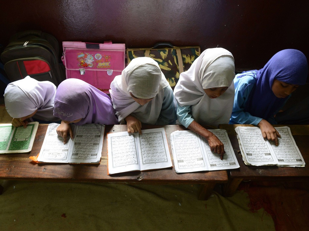 Indian Muslim girls reciting the Qur'an in their classroom at Madrasatur-Rashaad religious school in Hyderabad. (Photo by Noah Seelam)  I just love how the photographer included the variety of backpacks in this photo. It's what makes it special — and relatable to the Western observer who might easily focus in on the religiosity of the girls studying. I see a young schoolgirl out my front window in Minneapolis who is carrying a similar Hello Kitty bag.  ~Trent Gilliss, chief content officer
