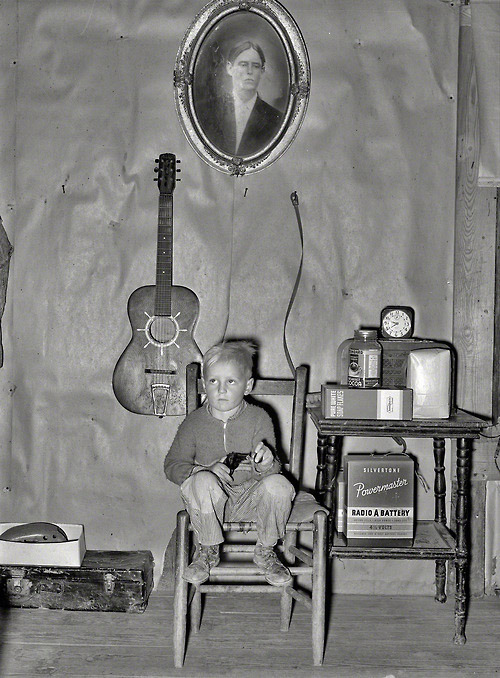 Son of tenant farmer in corner of living room, Sunflower plantation, Pace, Mississippi, January, 1939 Russell Lee