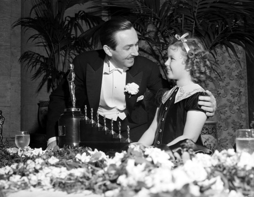 Walt Disney and Shirley Temple at the 11th Academy Awards, February 23rd, 1939. Disney received an honorary Oscar for Snow White and the Seven Dwarfs consisting of one regular statuette and seven miniatures.