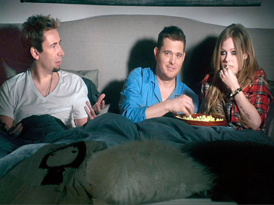 nparts:  Michael Buble gets in bed with Chavril To announce he will be hosting the 2013 Juno Awards, and eat Avril's popcorn. Watch the 30-second clip, which aired during last night's Super Bowl, here: natpo.st/Uoc5Qf