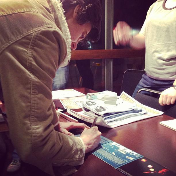 "Tig signs a CD that is in my possession. (By the way, I didn't take the photo, the person who runs the ""F Yeah Tig Notaro"" Tumblr page took it.)"