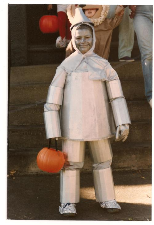 """I have always been terrified of the Wizard of Oz. My mom made me this costume at age 8 to go along with my siblings and cousins as a group for trick or treating that year. Because every 8 year old girl wants to be the Tin Man for Halloween? My ""body"" was made of a Styrofoam container a rose bush came in. I couldn't sit or go to the bathroom all day."" — Nina Schmidt, age 35. (Photo at age 8.) Have a great Oz photo? Click here to submit it to NPR's Backseat Book Club."