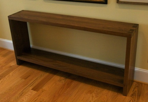conorstinson:  A modern hand-cut dovetail walnut console. This piece was made as a commission for Hill Country Woodworks earlier this spring. While simple in form, this console featured challenging joinery. The thickness of the wood meant all the existing Hill Country jigs were too small. From there on, I was on my own, cutting all of the tails using a table saw and my chisels and a router with a home-made jig for the pins. The lower shelf was joined to the walls with sliding dovetails. The console was the third of three pieces I made for these Hill Country customers. Below the console you'll see a dining room table, also in walnut, that I made for them last fall. The console and the dining table are both in their dining room, while the second of the three (a six drawer dresser) lives in an upstairs bedroom. That dresser was featured on this blog back in February.