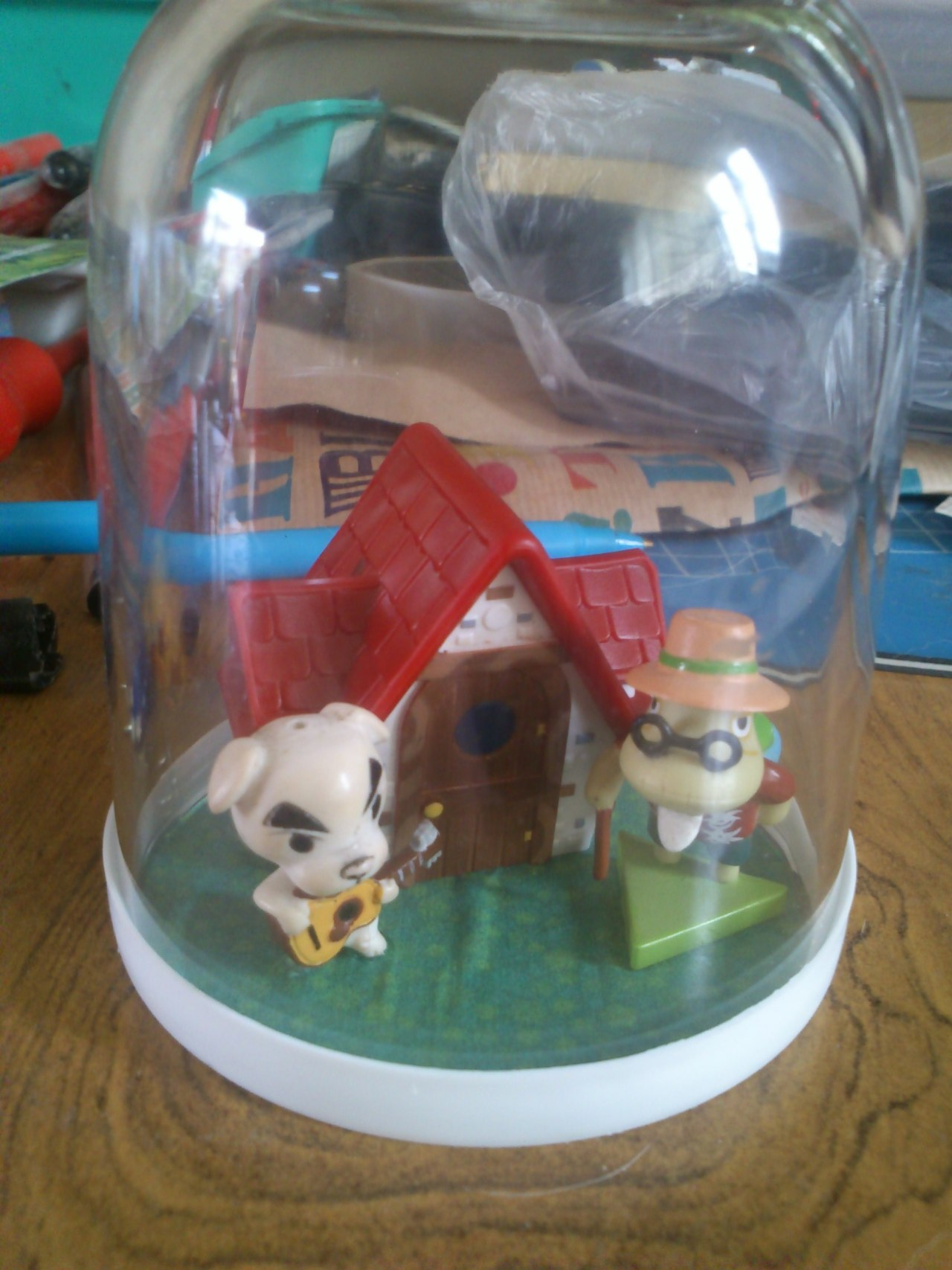 So I made this in like 5 mins.. Its a small Nutella glass, upside down. Printed out some AC grass and glued it to the bottom Glued in the House and Tortimer I got free with ONM Took KK off a keyring thing and glued him in too Tadaaah! AC Diorama!