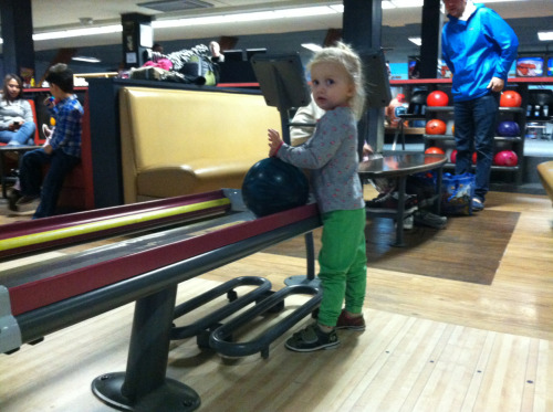 Rosemary took to the lanes for her first-ever bowling experience today. They even had tot bowling shoes that were only one size too large.  The alley had bumpers that automatically popped up when it was her turn, ramps to roll the balls down, and special little 6-pound balls for kids.  She enjoyed it for a while, but 6 people bowling on a game kinda took a while a boredom set in. Kid bowled a 92!