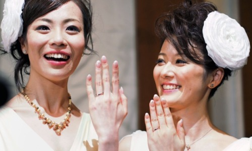 Koyuki Higashi and Hiroko smile as they show their marriage rings at their wedding reception in Tokyo. Two lesbians have become the first gay couple to tie the knot at Tokyo Disney Resort, both wore white dresses despite an initial ruling that one had to wear men's clothes. The event was the first gay wedding in the popular amusement park even though gay marriage has no legal standing in Japan. Photograph: Tatsunari Ueno/AFP/Getty Images