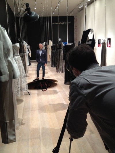 Francisco Costa shooting a portrait, surrounded by a special exhibition featuring looks from the Spring 2013 Calvin Klein Collection and select custom-designed celebrity dresses.