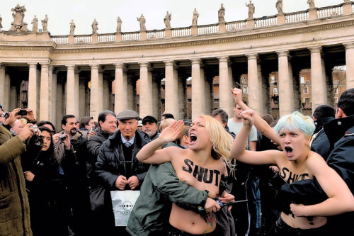 "Vatican City: Naked FEMEN Activists Disrupt Speech By Pope Benedict XVI Gotta love them. Joe.My.God. reports:  Yesterday topless Ukrainian activists FEMEN disrupted a Vatican City speech by the Pope by disrobing and screaming ""Homophobe! Shut up!"" at the little man in the window. Police moved in quickly and one woman attending the speech repeatedly smacked a protester with her umbrella. Below is FEMEN's own video of the action, which begins with a strategy session. Cube dwellers should note that there are boobies ahead."