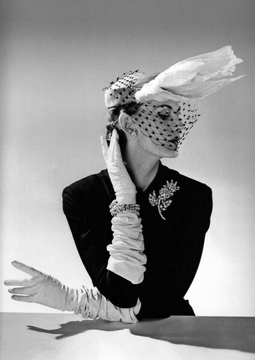 Model wearing a hat with veil and gloves, 1951. Photo by Willy Maywald.