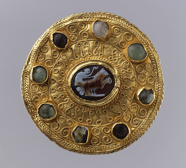 Disk Brooch with Cameo and Cabochons, cameo 100–300, brooch ca. 600Roman (cameo), Langobardic (mount) This cameo repeats a familiar classical type, but its energetic angular forms are a shorthand approximation of the earlier conception. Like some other nomadic tribes, the Lombards, or Langobards, the Germanic people who invaded northern Italy in the sixth century, prized Greco-Roman gems of earlier times, both preserving stones and displaying them by having them mounted in jewelry.  These gems were no doubt valued for their antiquity as well as their local character, as they linked their Langobardic wearers to the illustrious peoples who preceded them on the Italian peninsula.