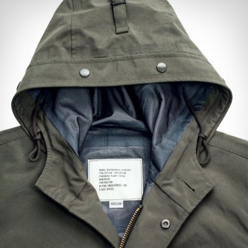 The Ace Hotel x Alpha Industries Waterproof Fishtail Parka — up now on our shop and on the handsome shoulders of our New York bellmen — is designed to breathe easy even while it keeps you warm and dry, based on the classic US Army M-65 Fishtail parka. The nylon shell is seam-sealed with an adjustable hood and waist for easy layering options in all wet weather conditions. The classic fishtail bottom can be snapped up. Soldiers of the olden days used to wrap the tails around their upper legs for freedom of movement and an additional waterproof surface. You can too if you want to.