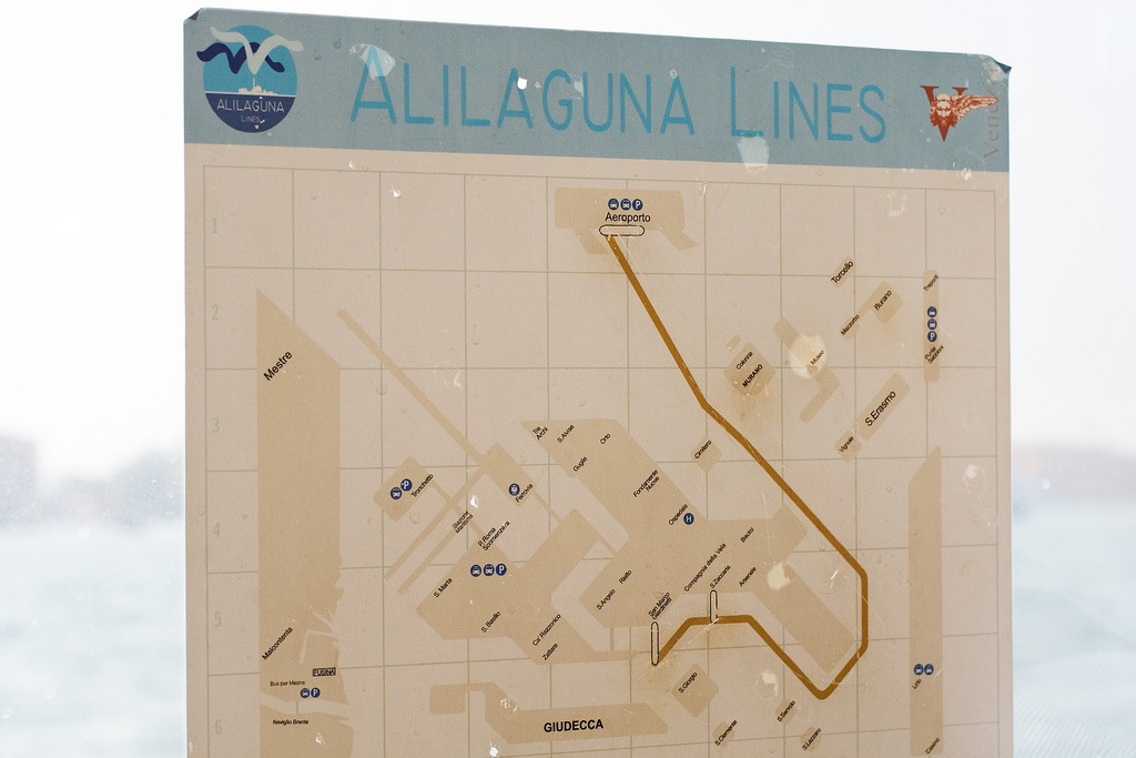 "Historical Map: Alilaguna Gold Line, Venice, 2006 We've featured Venice's public transportation ferry map previously (February 2012, 2.5 stars), but here's an interesting photo of a map by Alilaguna, a privately-run ferry and water taxi service. This map, dating back to 2006, shows only the Alilaguna Linea Oro (Gold Line), running from the airport to St. Mark's Square. Interestingly, this express route no longer exists, leaving passengers to lake the slower, local Linea Blu to the heart of Venice instead. The map has some interesting Vignelli-esque aesthetics, with the lagoon islands reduced to simplified, blocky shapes (as well as beige water!). The execution works well for Venice itself; less so towards the edges of the map. There's too much fussy detail over on the left side of the map near Malcontenta, and the way the mainland is strangely truncated makes Mestre and the airport look like they're also located on islands. Global warming, perhaps? Production-wise, it's obvious that this map has been created by simply deleting the other Alilaguna lines from a master map, which leads to the three ""station"" markers shown being extremely long for no apparent reason. The indeterminate angle the route line takes from the airport down towards Murano is also a little odd-looking, given the strong 45-degree design aesthetic of the map. Our rating: Nice concept, huge potential to be visually striking — but a shame about the uneven execution. Two-and-a-half-stars.  (Source: dr_loplop/Flickr)"