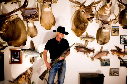 A Colorado hunter and gun enthusiast holds a shotgun and poses for a portrait surrounded by mounted animal heads he has killed at his home in Lakewood. (CNN Photos: Gun culture in Colorado – Matt Slaby/LUCEO)