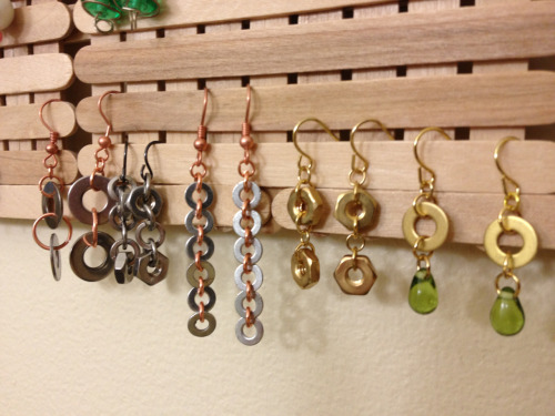 "Here's my current collection of hardware earrings. When I wear the brass ones, I walk around all day growling, ""I've got brass nuts."" and then giggle maniacally and then I have to explain myself.   Also pictured, earring hanger made out of Popsicle, err, ""craft"" sticks and then nailed to the bathroom wall.  I have a bead problem."