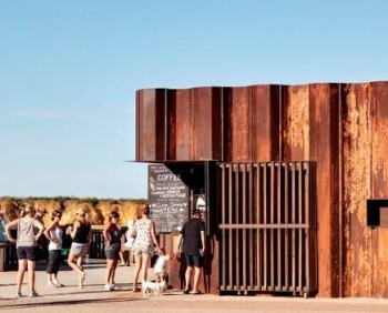 A beachside kiosk in Torquay, Australia sets itself apart as a local architectural landmark by artfully making use of reclaimed flood barriers as its exterior walls. Designed by Tony Hobba Architects, the Third Wave Kiosk stands out on the shoreline whilst blending visually with the landscape, thanks to the use of upcycled sheet piles. Knstrct reports that they were used as temporary formwork for sandbanking overflowing rivers during flooding. The architects wrapped them around the building to create a weathered, wave-like effect.  More: Beachside Coffee Bar Made Of Reclaimed Flood Barriers [Pics] - PSFK