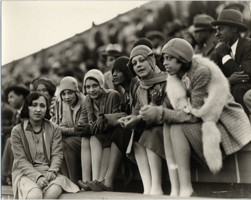 VINTAGE FASHIONISTAS II | 1922 Six Howard University students sitting in Griffith Stadium watching football game. All but one of the women wear cloche hats and sporting flapper style outfits. Addison Scurlock, photographer. Image courtesy of the American History Museum, Smithsonian Institute.