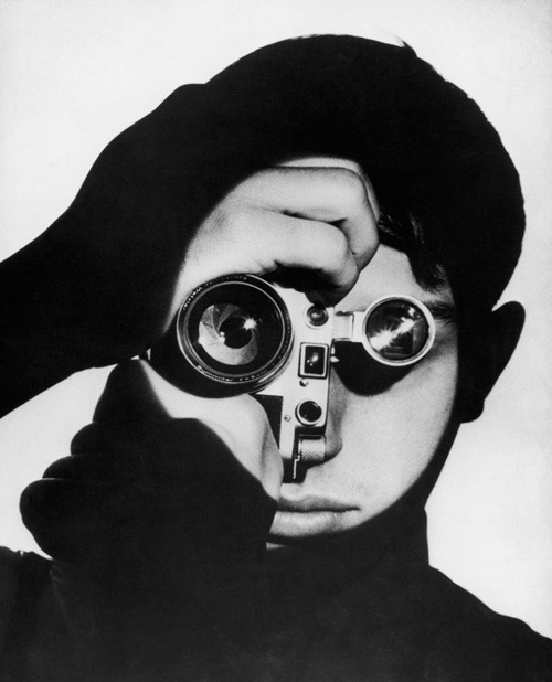 Photographer Dennis Stock holding a camera in front of his face, 1955 by Andreas Feininger