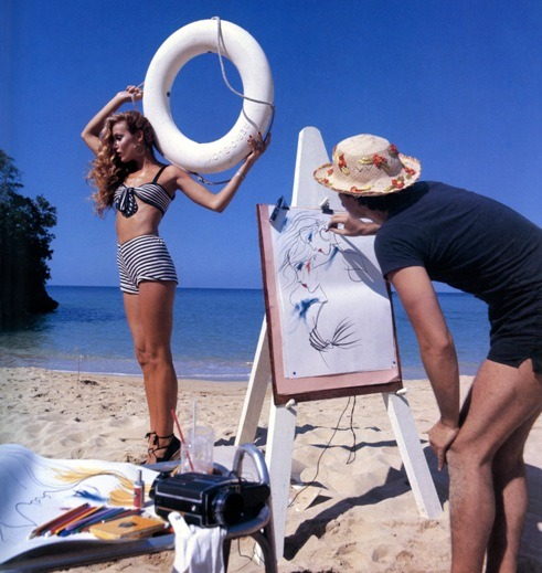 Jerry Hall on the beach in Jamaica posing for Antonio Lopez who was drawing her as a mermaid.