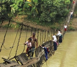 Crossing the (collapsed) bridge to school. Sumatra, Indonesia. Photo by Panjalu Images. Source.