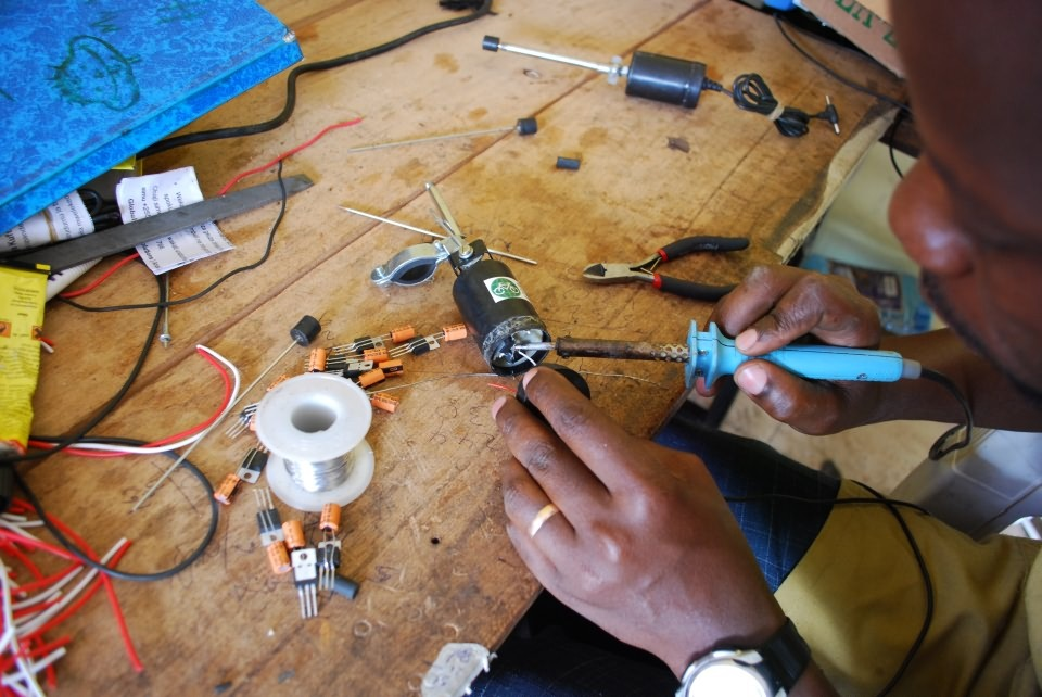 anamasnoname:  Bicycle Phone Changer In Tanzania, the majority of people live without electricity, yet a third of the country uses mobile phones. Bernard Kiwia, a trained electrician and vocational-school instructor, collaborated with the for-profit social enterprise Global Cycle Solutions (GCS) to design a phone charger from scrap bike and radio parts. Made from spokes, brake tubes, clamps, motors, and capacitors, the device generates power when its roller comes in contact with the bike's spinning wheel as one rides it