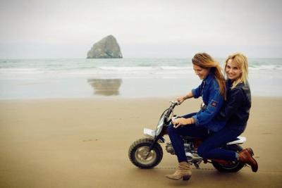 Tori Tuesday gives her pal Amy Callahan a minimoto ride on Cannon Beach on the Oregon Coast. Photo by Ray Gordon.