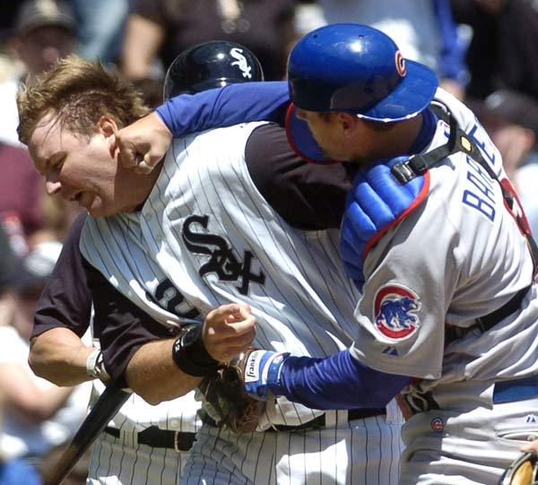 On this day in 2006, Michael Barrett shows his displeasure at A.J. Pierzynski by punching him in the face. The incident igniteed a bench-clearing brawl between the White Sox and Cubs which led to a 15-minute delay and four ejections during the White Sox's 7-0 victory at U.S. Cellular Field. (AP)