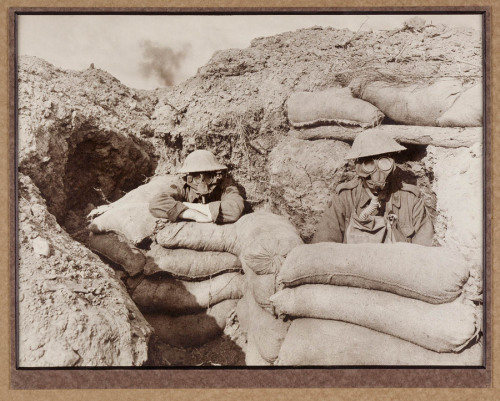 Australian Infantrymen sit in 'funk holes' during a gas attack on the Western Front. These two men appear to be wearing the Small Box Respirator mask. c. 1917.
