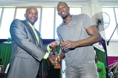 Usain Bolt (right) hands over the keys for a school bus to Dr Mark Nicely, principal of the William Knibb Memorial High, yesterday. (Photo: Phillip Lemonte)Read more: http://www.jamaicaobserver.com/westernnews/Usain-s-Gift-#ixzz2EoDiaF74