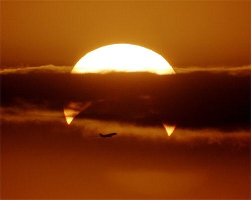 akcdiary:   Partial Solar Eclipse with Airplane   Image Credit & Copyright:  Phillip Calais  Explanation:  It was just eight minutes after sunrise, last week, and already there were four things in front of the Sun. The largest and most notable was Earth's Moon, obscuring a big chunk of the Sun's lower limb as it moved across the solar disk, as viewed from Fremantle, Australia. This was expected as the image was taken during a partial solar eclipse — an eclipse that left sunlight streaming around all sides of the Moon from some locations. Next, a band of clouds divided the Sun horizontally while showing interesting internal structure vertically. The third intervening body might be considered to be the Earth's atmosphere, as it dimmed the Sun from its higher altitude brightness while density fluctuations caused the Sun's edges to appear to shimmer. Although closest to the photographer, the least expected solar occulter was an airplane. Quite possibly, passengers on both sides of that airplane were contemplating the unusual view only visible out the eastern-facing windows.Source: apod.nasa.gov