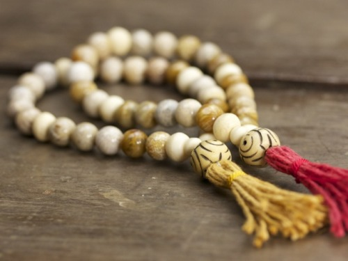 New: Fossilized Coral and Bone Mala Fossilized Coral is formed when ancient coral becomes buried and replaced with agate through the process of permineralization. This grounding and calming stone is known to facilitate intuition, imagination, visualization, bravery and wisdom. Learn more and purchase at Japa Mala Beads