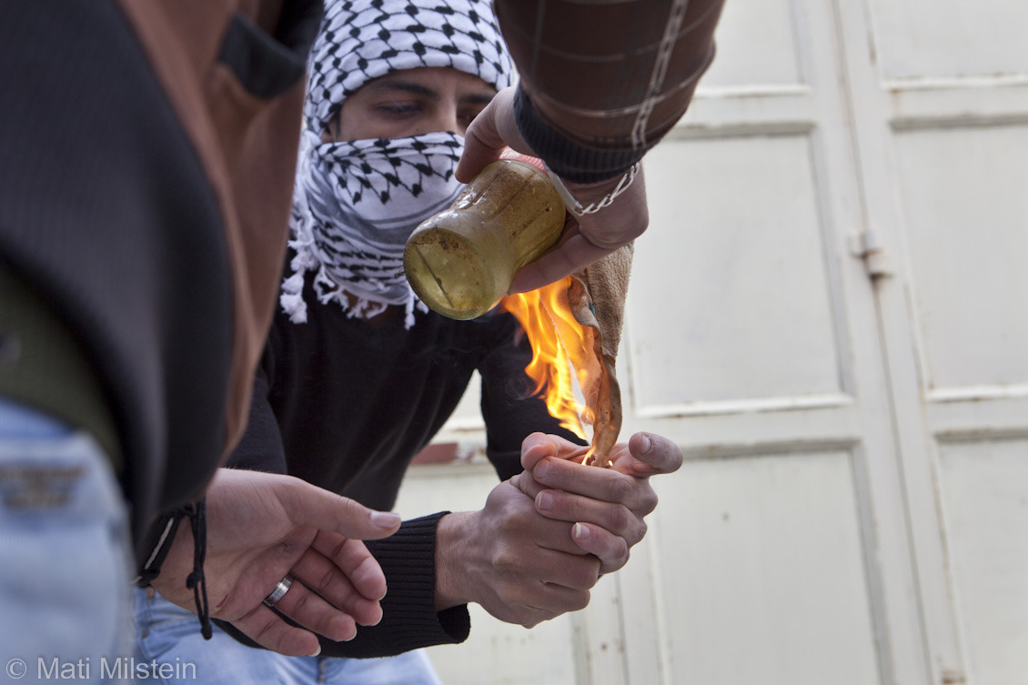 Fire and Smoke II  Palestinian men light a firebomb during a protest near the West Bank city of Ramallah in support of Palestinian prisoners being held in Israeli detention.