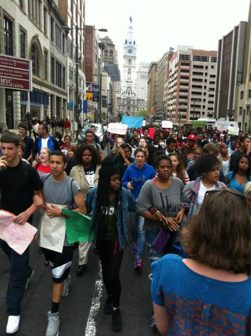 "How a few Philly high school students organized themselves into a few hundred in four daysMay 9, 2013 It began, not surprisingly perhaps, with a modest online message. About two weeks ago, school district officials had announced, once again, a serious hole in the District's budget and had laid out, once again, severe cuts that would be implemented if a roughly $300 million hole wasn't filled — this time invoking layoffs and cuts to programs, especially arts and extracurricular. And as students pondered cuts to their favorite programs, the irony that last Friday would mark ""Teacher Appreciation Day,"" was not lost upon them. Before news of the proposed cuts reached them, says Teyin Tseng (upper right), a member of the student council at the Philadelphia High School for the Creative and Performing Arts, ""Our plan was to see how much money we had and see if we could buy flowers for every teacher."" ""But then the budget [was unveiled] — and we decided to do this."" So, on Friday, another CAPA student, Maureen Smith (lower center), created a new Facebook page: Silenced Students March — announcing a plan by her and some of her classmates to protest the threatened cuts. She opened with something of a rallying call: ""As students we are fed up and want to be heard. Its OUR education and WE should have a say in it. TUESDAY May 7th is teachers appreciation day, we are organizing a march to 440 North Broad Street, which is the school district building. Depending on your school's location you can choose a meeting area and then proceed to march to 440.We will all be meeting there by 4:30. There is strength in numbers."" The response — recorded online in blow-by-blow Facebook posts — was immediate, enthusiastic, and complex as any overnight organizing effort. Talking points were discussed; a deliberate effort to attract media and control the message was conceived. And there was, as there is in any organizing effort, vigorous debate over tactics and message: When some students announced a planned walkout; other students objected, worried the organized disobedience would undermine their credibility as a group — a debate which continues as some students contemplate a walkout tomorrow. A system was worked out: each school's protest contingent should nominate  a representative to contact. ""We have a huge network,"" explained Tseng outside the building. ""We all called each other, and we got a lot of schools to join."" ""I was contacted by Teyin over here,"" said Belal Shami (lower left), ""and he told me he needed my help. My role was to gather people from Franklin Learning Center and get them to the protest. … I brought roughly 35 people."" In a stretch of years in which there has been no shortage of protests outside 440 N. Broad, yesterday nonetheless marked the first time many of these students had ever done anything of the sort. And their motivations often went beyond their personal welfare. ""People are saying, 'You're a Senior,' why are you here?' Well, I have friends that I've made this year in lower grades,"" said Kelechi Ekwerike (upper left), for whom this protest was his first. ""For their education to be cut short, truncated, I will not stand for that. And if this carries on next year, if nothing is done, they [the School District] will not hear the end of it."" ""The sense in my class is a little bit like we're the last survivors on the Titanic,"" is how Samantha Ho (upper center), a junior at Masterman High School, put it. ""We survived. But I have a cousin who's going to be first year at Masterman —  I can't really imagine that place without extracurricular activities. That's where people connect."" ""My little brother, my sister — I don't care about myself,"" said Spencer Nguyen (lower right) from the Palumbo Academy of Art. ""This is for future generations."" About two hours after the protest had started, a small knot of these students remained outside school headquarters, huddled as they debriefed and planned for whatever comes next. ""I'm more than happy with the turnout,"" acknowledged Facebook event creator Maureen Smith. ""It really does speak volumes, that young people can make a difference."" SourceFrom the Philadelphia Student Union: Today, hundreds of students walked-out of school and took to the streets. We rallied at City Hall to tell City Council that we need funding for our public schools. We have had enough budget cuts. We marched down Broad St. to 440. Students are ready to fight back against budget cut backs. Get ready to see a lot more of us next time."
