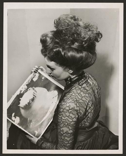 "Atomic Bomb Hair Style ""Liliana Orsi, a 22-year-old beauty in Rome, Italy, displays her new atomic hairdo and the photo of the atomic blast which inspired it. It took a hair stylist 12 hours to arrange Liliana's coiffure, so it's not recommended for daily wear. It's an old fashion and something dangerously new."" - Acme Newspictures"