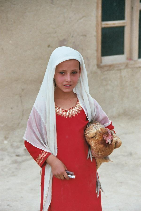 An Afghanistani girl with a rooster, Michael Luongo
