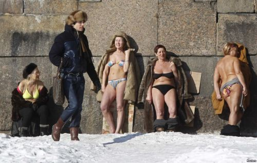 People sunbathe by the wall of the Peter and Paul Fortress in St. Petersburg, Russia.  Brrrr.
