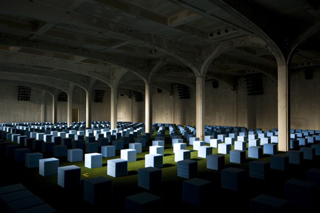 ylide:  OMA, Prada Men's SS 2012 Venue, 2012  The field is a commentary on the audience, transformed from indeterminate crowd to regimented, possibly anxious, isolated individuals. Each guest becomes a challenge for the new fashion; each confrontation becomes highly personal. It is based on a zero degree approach: a spatial system as opposed to an elaborated design. Artificial grass covers the floor. Light is provided by 16 panels of 30 PAR lights each, vaguely resembling stadium lighting systems.