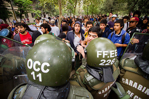 "Chilean students rise again: Protests mark start of school yearMarch 7, 2013 An estimated 300 people assembled in downtown Santiago on Thursday for the academic year's first student protest, which quickly turned into a violent confrontation between demonstrators and Chile's national police force, the Carabineros. The protest was not authorized by the metropolitan government nor the Carabineros and unlike many student marches, was not organized by the umbrella student organization Confech. Simultaneous demonstrations also took place in Concepción, Valparaíso and Valdivia.Soon after the protest commenced, police urged the demonstrators through megaphones to disperse from near the Manuel Rodríguez monument in Plaza Baquedano. However, a minority of hooded youths, nicknamed ""encapuchados"" in Chile, forced the amassed Carabineros into action by throwing rocks and other missiles. The chaos that followed saw student groups fleeing from the resulting tear gas, paintballs and water cannons released from surrounding armored police vehicles.The retreating students chanted in unison ""Chilean education is not for sale"" and ""the education system of Pinochet will fall,"" in reference to the defunct dictator who established the current educational framework.In a bizarre confrontation, musicians playing saxophones and clarinets, accompanied by several female belly dancers, performed just feet away from the assembled riot police in an act of defiance that was met with amusement from the surrounding hordes of students.The gathered demonstrators lashed out at the highly privatized Chilean higher education system and its inaccessibility for poorer students.""What we want is an end to profits and free access to high quality education,"" said one participant.Another young protester, Iván, went further and argued that the ongoing demonstrations reflected a wider discontent regarding Chile's deep-seated ""financial inequality between rich and poor.""Official figures released by Carabineros claim that 30 students were arrested during the protests. Unknown demonstrators also reportedly threw stones and left graffiti on the office of conservative presidential candidate Laurence Golborne.Chile's education system has long been criticized for its high costs, long duration and low levels of public funding, which leaves many graduates with crippling debts. Wednesday's demonstration is just the most recent within a student movement that sprung to life in 2011, demanding a fairer and more accessible education framework in the country. Source"
